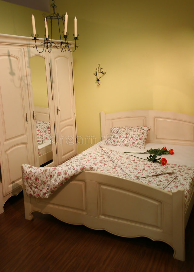Cream bedroom with roses. And candles stock image