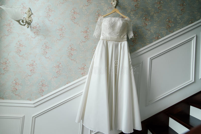 Cream bride hang on the lamp against the wall next to the stairs royalty free stock image