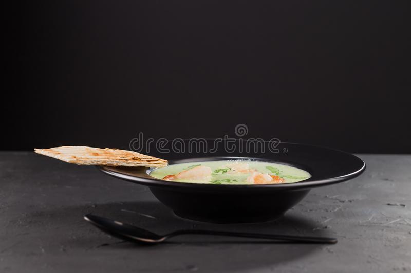 Cream broccoli soup with shrimp in a beautiful black plate on a dark background. Seafood dish. Selective focus. royalty free stock images