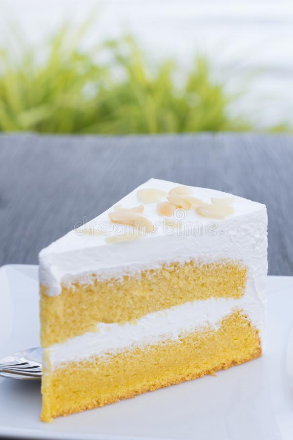 Cream butter cake in white dish on wooden table with sea background royalty free stock photo