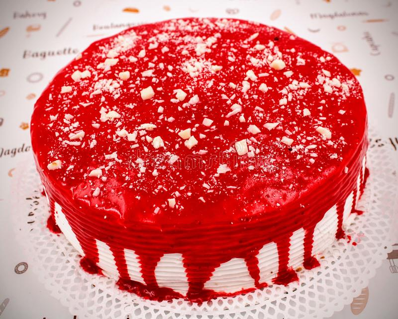 Cream cake with strawberry syrup. And white chocolate shavings stock photo