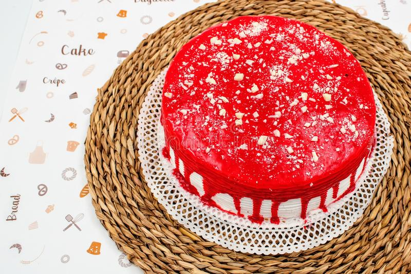 Cream cake with strawberry syrup. And white chocolate shavings royalty free stock images
