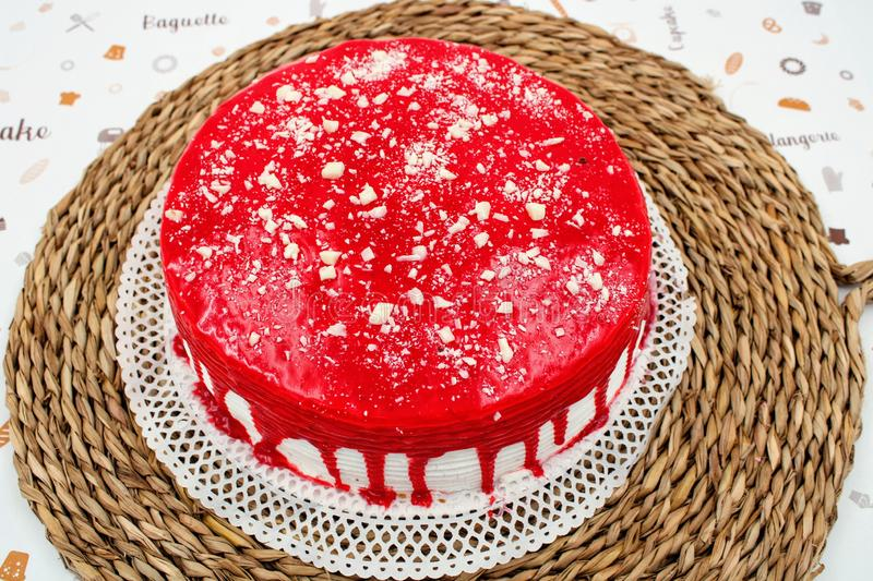 Cream cake with strawberry syrup. And white chocolate shavings royalty free stock image