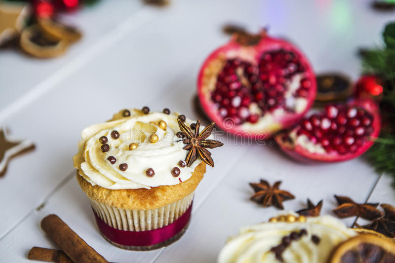Cream cakes, cupcakes cut red pomegranate, cinnamon, dried lemons lie on white wooden table royalty free stock image