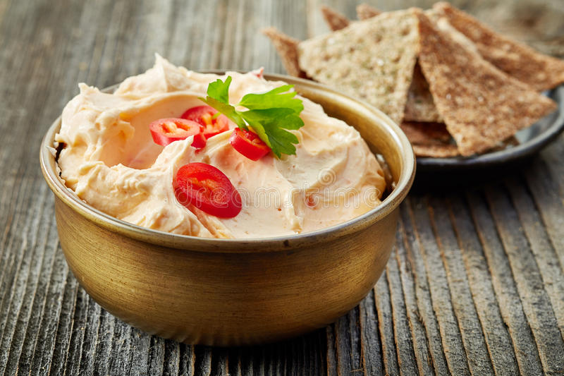 Cream cheese with chili and tomato, dip sauce. Bowl of cream cheese with chili and tomato, dip sauce on wooden table royalty free stock photo