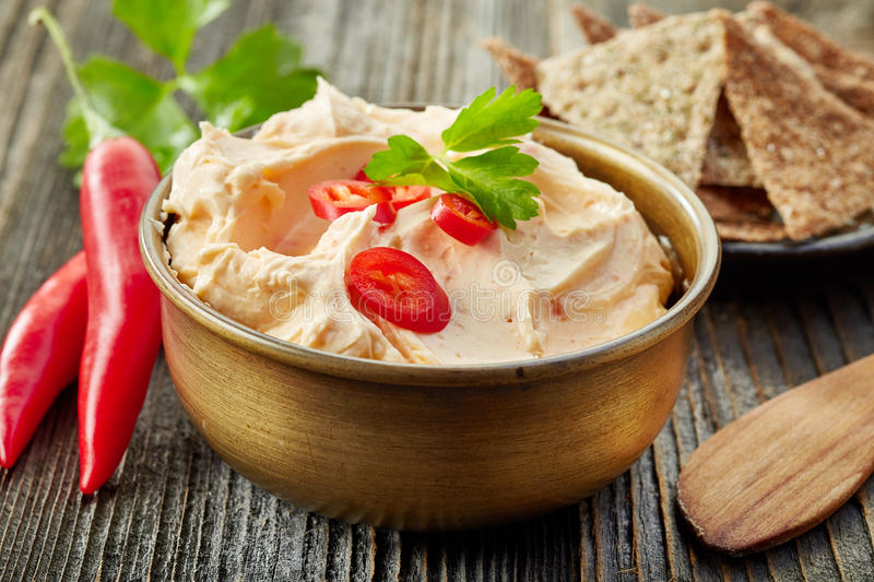 Cream cheese with chili and tomato, dip sauce. Bowl of cream cheese with chili and tomato, dip sauce on wooden table royalty free stock images