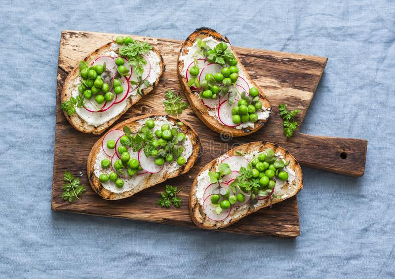 Cream cheese, green peas, radishes and micro greens spring sandwiches on a cutting board. Healthy eating, slimming, diet lifestyle stock photography