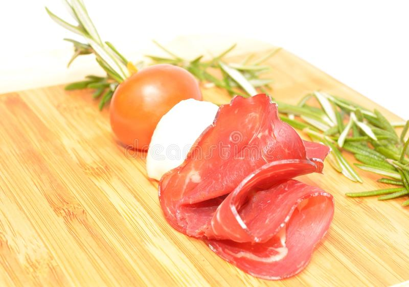 Cream cheese roll ups appetizer with prosciutto and mozzarella. On white stock images