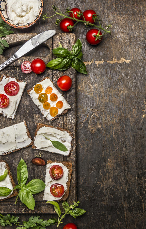 Cream cheese sandwich with seasoning and tomatoes on rustic wooden background, top view, border, vertical. Healthy, diet or stock photos