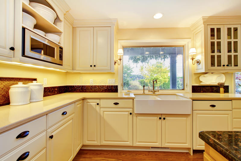 Cream color kitchen with large white sink and classic design. royalty free stock photo