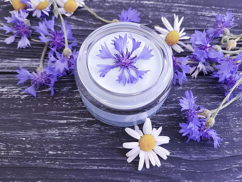 Cream cosmetic flowers cornflower, product natural essence camomile alternative on a dark wooden background royalty free stock photography