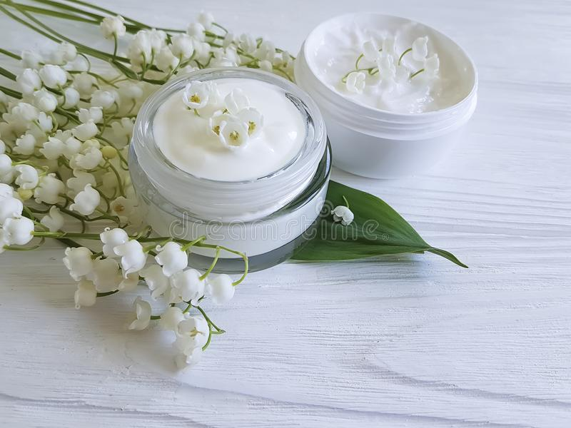 Cream cosmetic lily of the valley relaxation ointment aromatic rustic beauty on a white wooden background royalty free stock photos