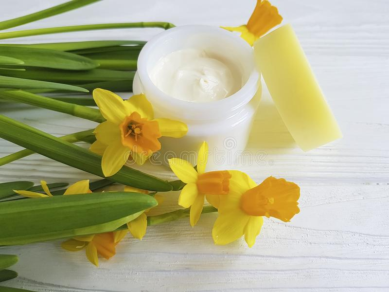 Cream facial skin cosmetic extract pot care narcissus ointment rustic organic daffodil on white wooden treatment. Cream cosmetic facial narcissus on white wooden royalty free stock images