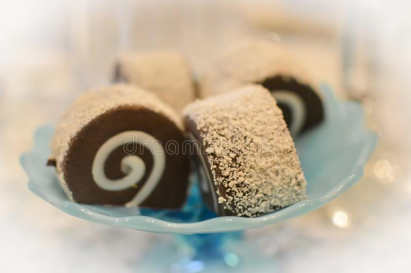 Chocolate Cake Roll Ups on Pretty Blue Platter. Cream filled, chocolate cake roll ups covered in powdered sugar on a baby blue cake platter with Christmas lights royalty free stock photo