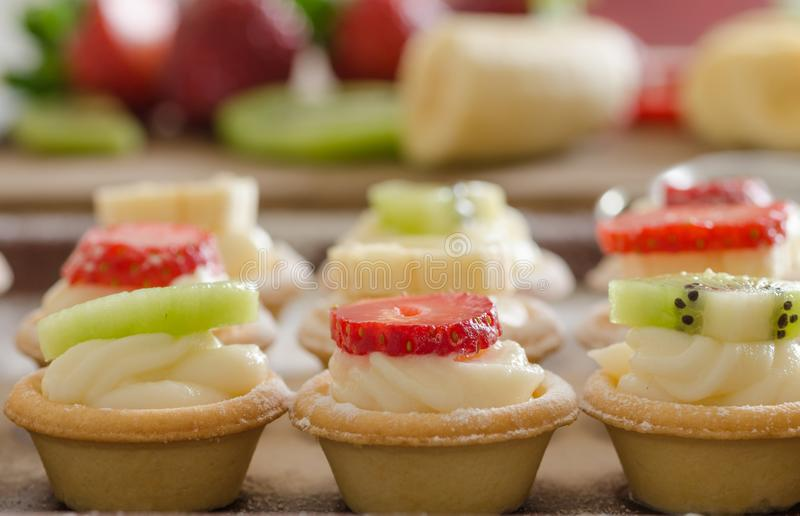 Cream filled tartlets. There are strawberries, kiwi and bananas. On the surface. There are fruit in the background stock photography