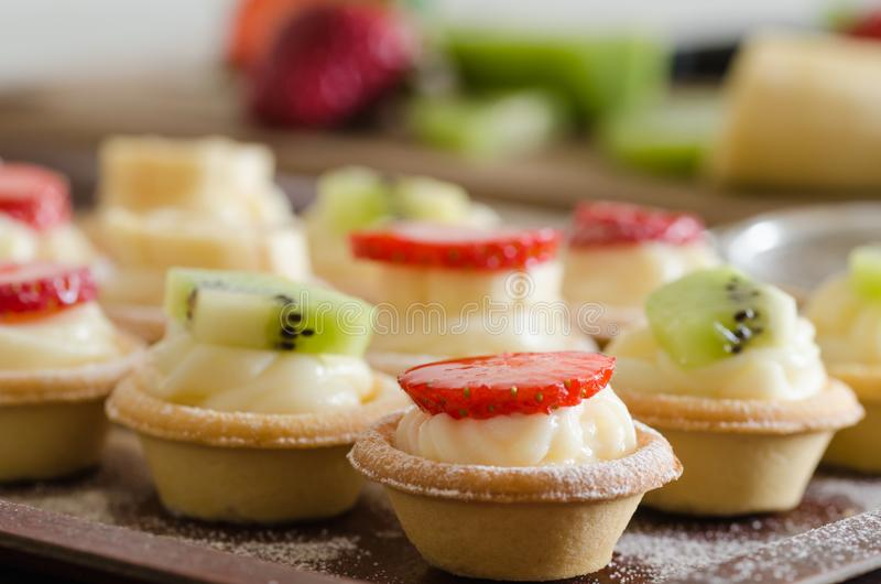 Cream filled tartlets. There are strawberries, kiwi and bananas. On the surface. There are fruit in the background royalty free stock image