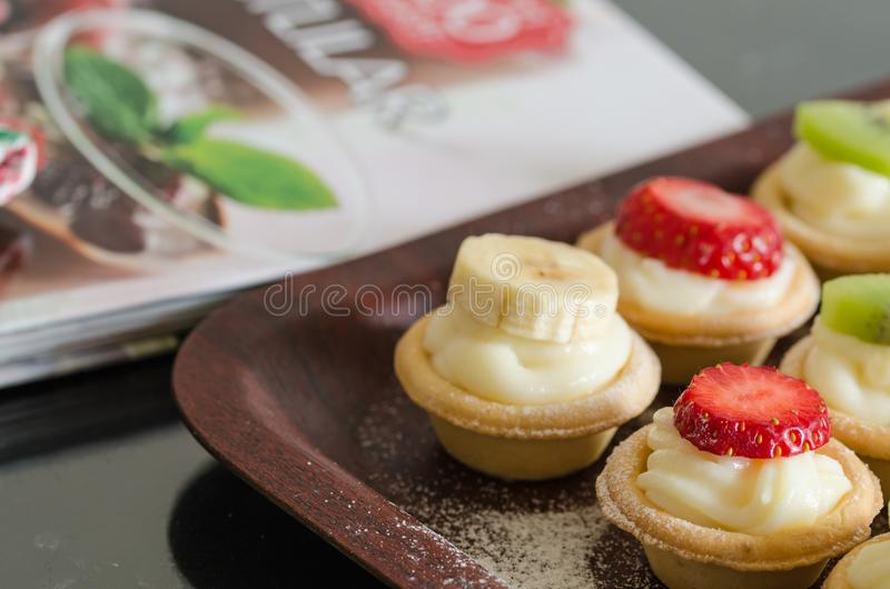 Cream filled tartlets. There are strawberries, kiwi and bananas. On the surface stock photos