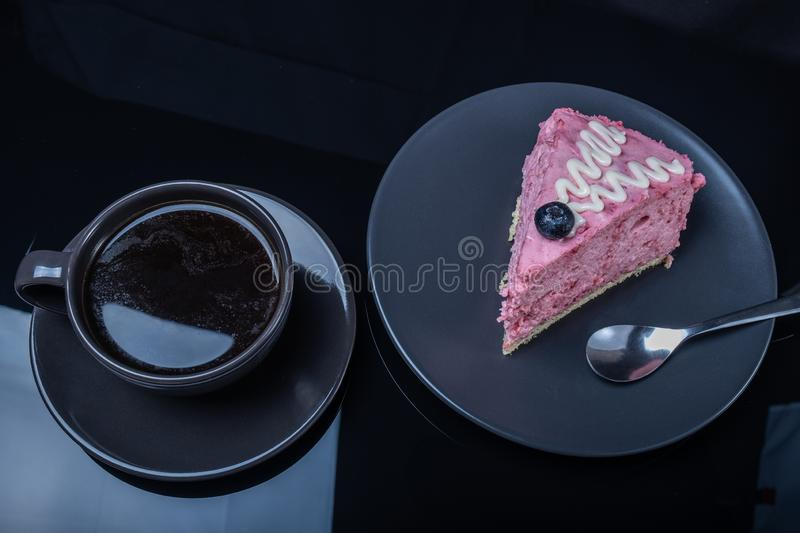 Cream fruit cake and a cup of black coffee on a black glass table royalty free stock photo