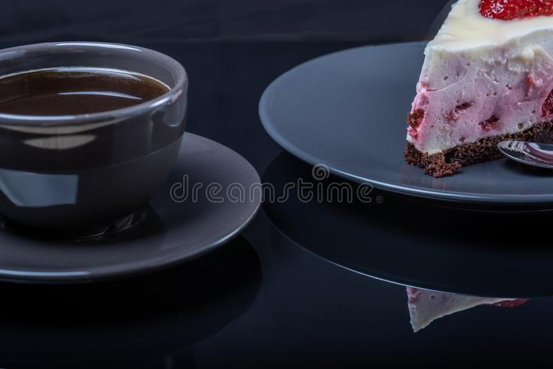 Cream fruit cake and a cup of black coffee on a black glass table royalty free stock photography