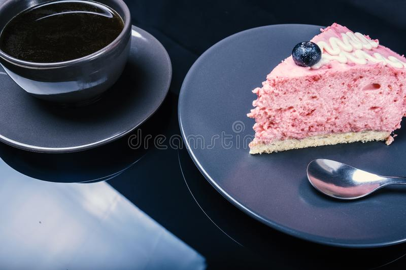 Cream fruit cake and a cup of black coffee on a black glass table stock photo