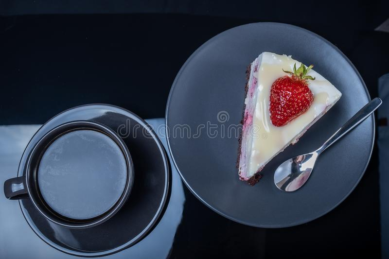 Cream fruit cake and a cup of black coffee on a black glass table royalty free stock photos
