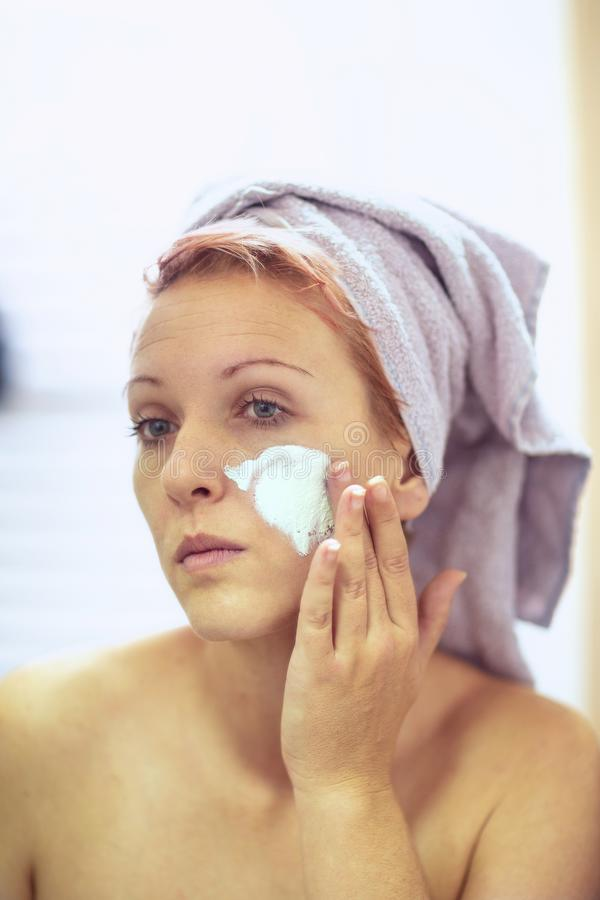 Cream on her face, mask on the face, problem skin - Smiling girl applying facial mask stock image