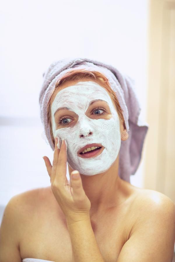 Cream on her face, mask on the face, problem skin - woman with a face mask royalty free stock photo