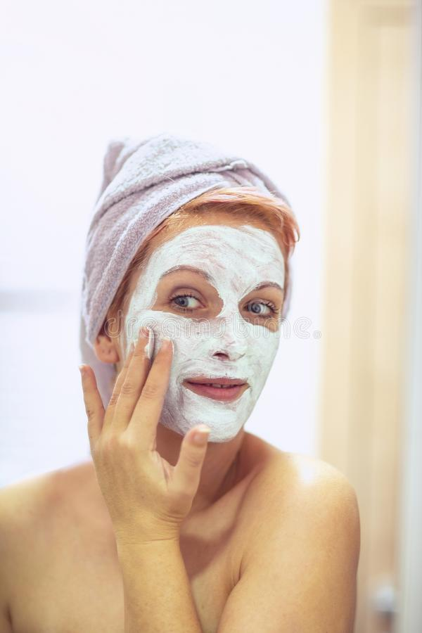 Cream on her face, mask on the face, problem skin - Smiling Woman applying facial mask stock images