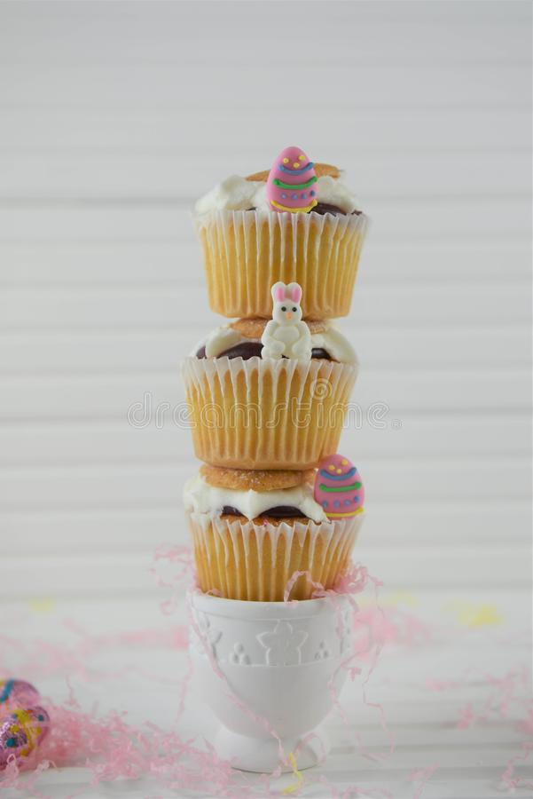 Vertical stack of Easter cakes on white in an eggcup. Cream jam and vanilla homemade cupcakes or fairy cakes with sprinkles. Stacked in a vertical heap with stock photos