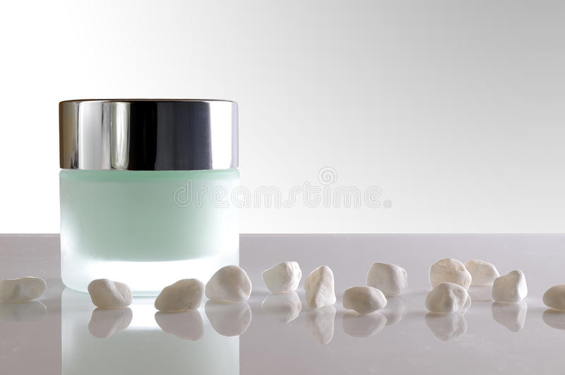 Cream jar closed and small white stones stock photo