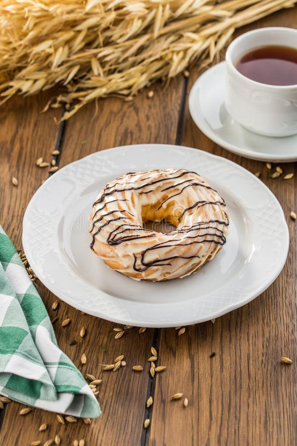 Cream puff rings with chocolate glaze choux pastry on wooden table royalty free stock image