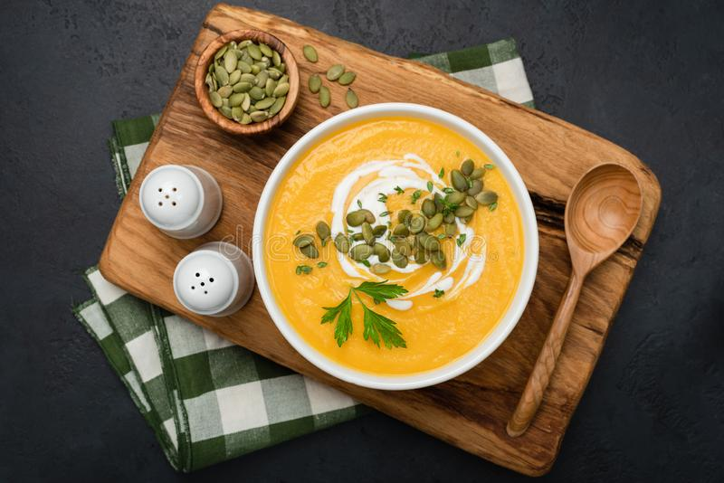 Cream of pumpkin soup in bowl on wooden serving board royalty free stock photos