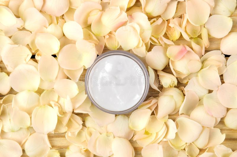 Cream in rose petals. Cosmetics for face and body in pink bottles with fresh roses. spa. top view royalty free stock image