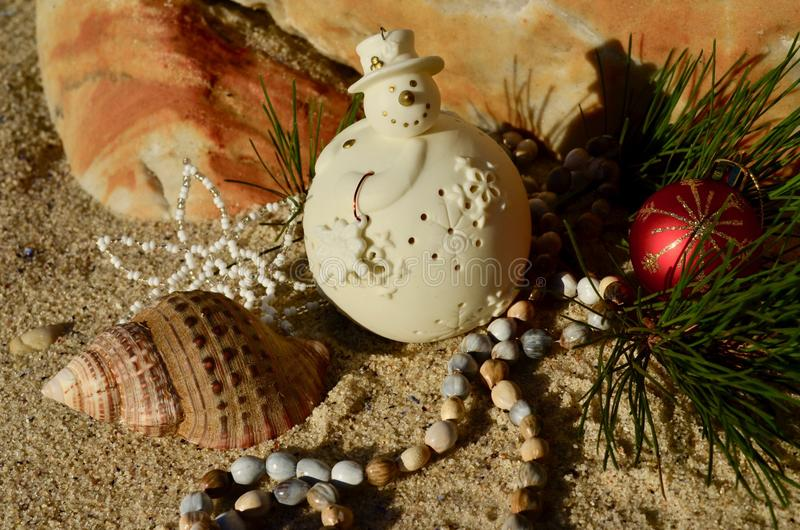 Cream snowman decoration on beach sand rock backdrop shell natural african beads red ball Christmas in July stock photo