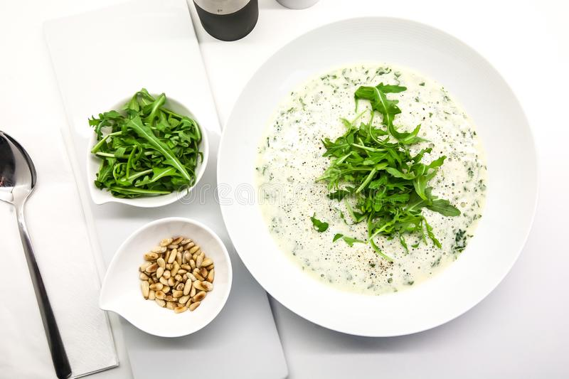 Cream soup with arugula and pine nuts in a white bowl stock photo