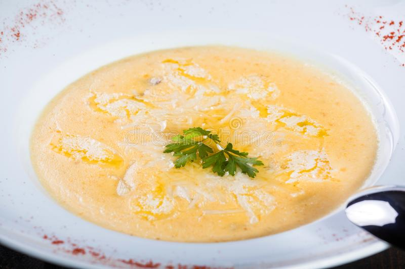 Cream soup with cheese parmesan, herbs and chicken on plate on dark wooden background royalty free stock photo