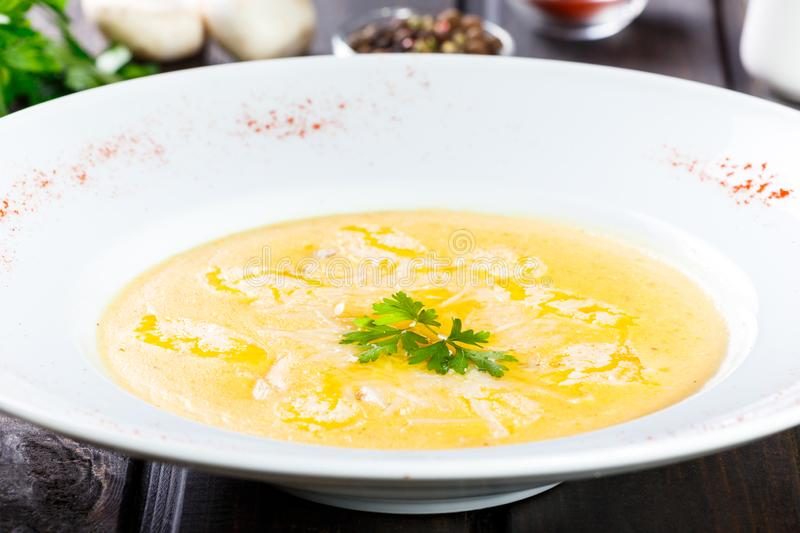 Cream soup with cheese parmesan, herbs and chicken on plate on dark wooden background. stock images