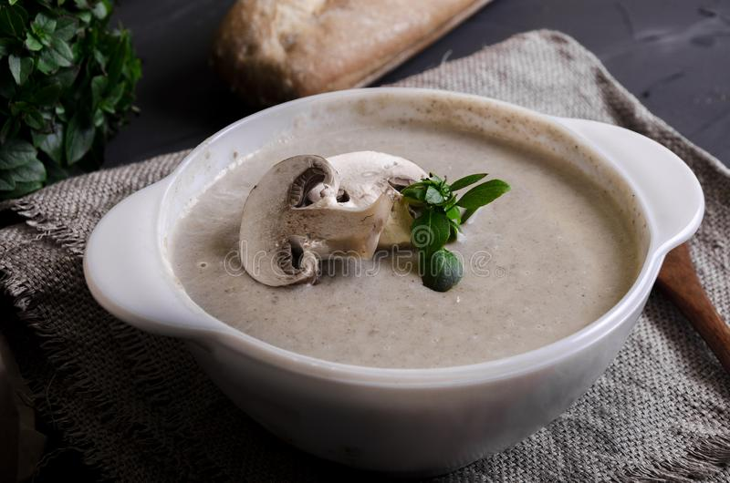 Cream soup made from mushrooms with bread. Cream soup made from mushrooms with crispy bread and oregano on black phone royalty free stock photos