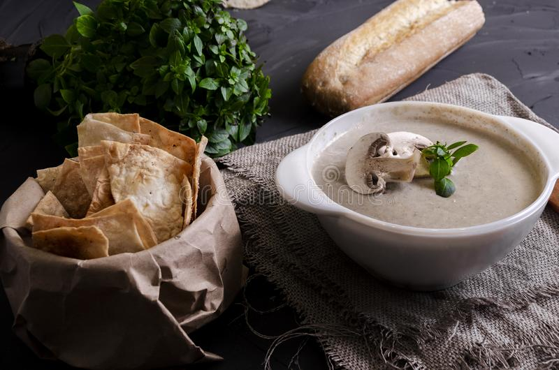Cream soup made from mushrooms with bread. Cream soup made from mushrooms with crispy bread and oregano on black phone stock image