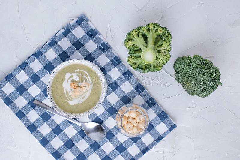 Cream soup puree with broccoli, cream and crackers. Lunch of vegetables on a light background. Plate and napkin on the table.  royalty free stock photos