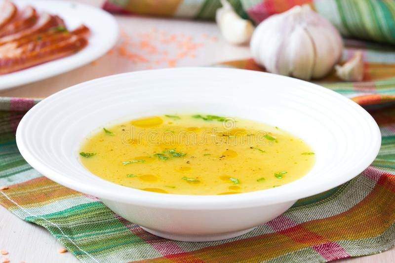 Cream soup of red lentil with smoked meat, duck, chicken stock photo