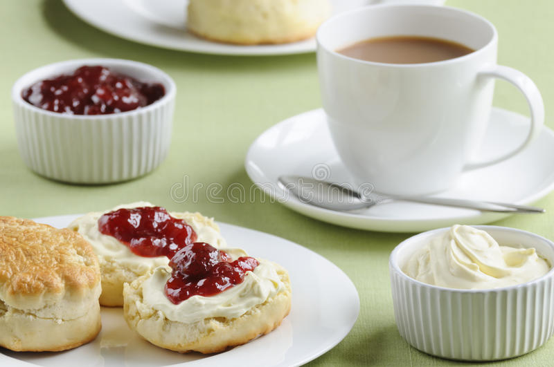 Cream tea. Traditional English cream tea of scones, clotted cream, strawberry jam and a cup of tea. These are served Devonshire style, with the jam on top