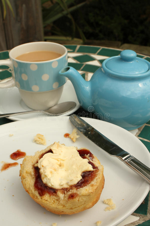 Cream Tea. Delicious home baked scone spread with jam and clotted cream served with a pot of tea for one in a bright blue and a spotted blue mug outdoors royalty free stock image