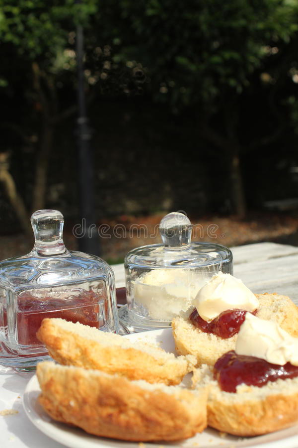 Cream Tea in the garden. Delicious home baked scone spread with jam and clotted cream to be enjoyed outdoors stock photography