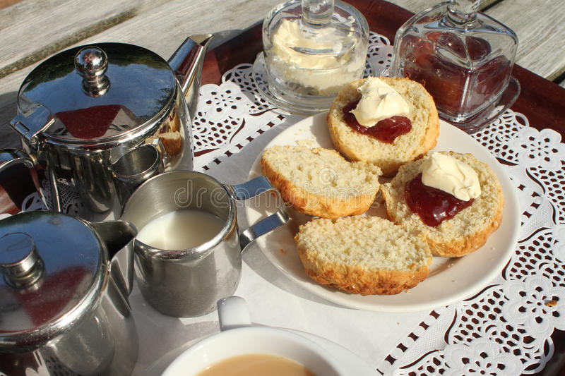 Cream Tea on a tray. Delicious home baked scone spread with jam and clotted cream to be with a silver pot of tea stock photo