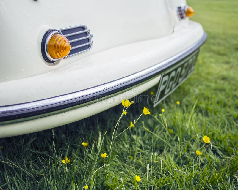 Cream vintage car in a meadow royalty free stock images