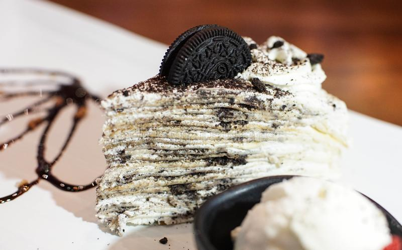 Crepe cake in an oreo flavor. Creamed filled crepe cake. Oreo flavor crepe cake topped with an Oreo cookie. A bowl of vanilla ice cream with cake royalty free stock image