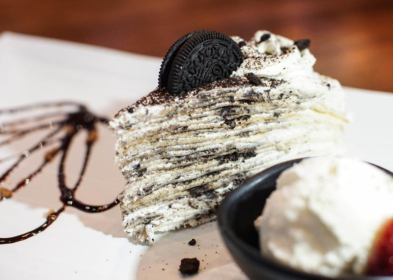Crepe cake in an oreo flavor. Creamed filled crepe cake. Oreo flavor crepe cake topped with an Oreo cookie with a bowl of vanilla ice cream royalty free stock photography