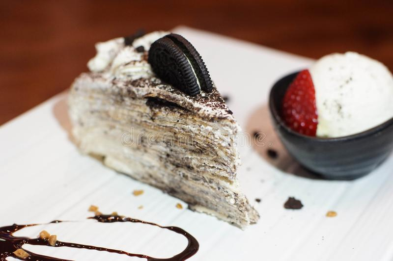 Crepe cake in an oreo flavor. Creamed filled crepe cake. Oreo flavor crepe cake topped with an Oreo cookie. A bowl of vanilla ice cream and fresh strawberry with stock image