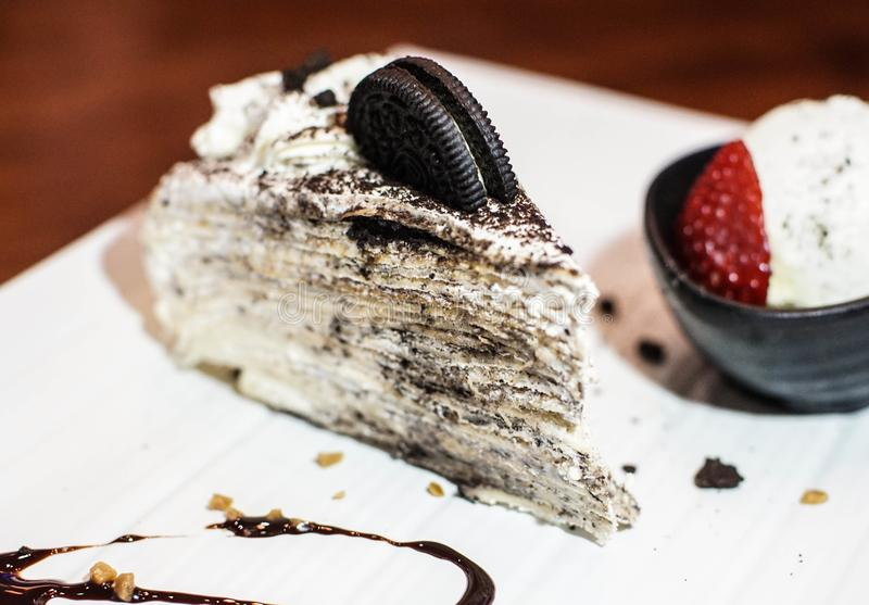 Crepe cake in an oreo flavor. Creamed filled crepe cake. Oreo flavor crepe cake topped with an Oreo cookie. A bowl of vanilla ice cream and fresh strawberry with stock images